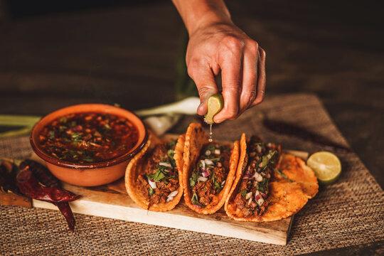 tabla  arreglada con tacos de birria, barbacoa y consome