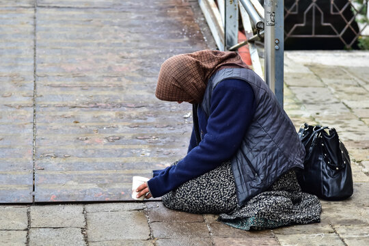 Beggar gypsy woman begging for money passersby kneeling on the ground