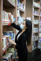 Beautiful Asian librarian woman  wear face masks  to prevent coronavirus, or COVID-19 she is...