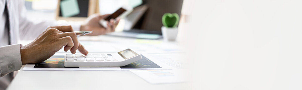 Businessman is using a calculator to calculate company financial figures from earnings papers, a businessman sitting in his office where the company financial chart is placed. Banner with copy space.