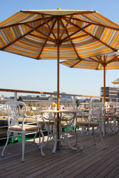 Elegant cast iron deck chairs and tables with sun umbrellas on outdoor pool deck of luxury cruiseship or cruise ship liner for al fresco buffet dining