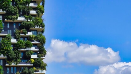 Low Angle View Of Buildings Covered With Plants Against Blue Sky