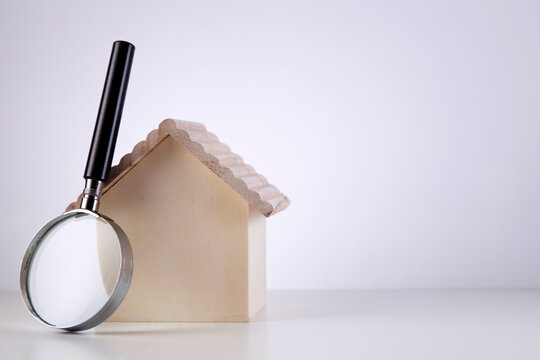 Close-up Of Magnifying Glass And Model House On Table Against White Background