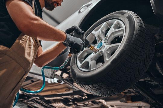 Auto mechanic changing car wheel.