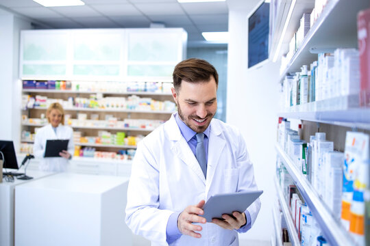 Handsome male pharmacist in white coat working in pharmacy store or drugstore. Checking medicines on his tablet computer. Healthcare and apothecary.