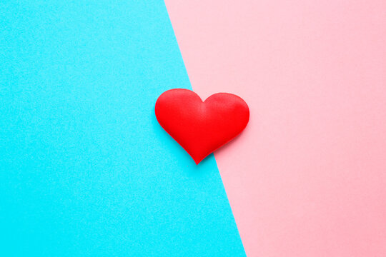 One bright red textile heart in middle on light blue pink table background. Pastel color. Love concept of boys and girls or men and women. Couples relationships. Closeup. Top down view.