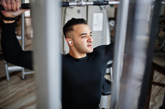 Muscular arab man training and doing workout on fitness machine in modern gym.