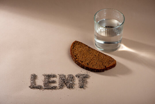 Lent Season, Holy Week and Good Friday concept - water, bread and text made of ashes..