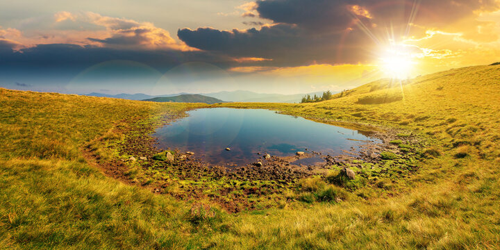 pond on the mountain meadow at sunset. wonderful summer landscape in evening light. grass and trees on the hills. ridge in the distance. beautiful wide panorama