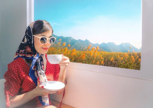 Beautiful woman in retro style. Sunglasses and silk scarf sitting by the window and sipping a tea in the afternoon.retro style with noise and grains effect.
