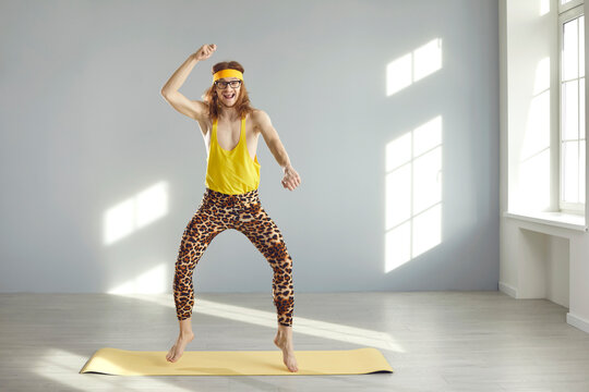 Skinny fitness nerd having fun during sports workout at home. Funny thin young guy in yellow sweatband and hilarious leopard leggings looking at camera and smiling while dancing and jumping on gym mat