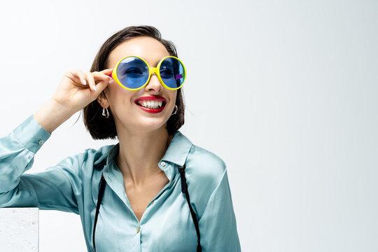 Portrait of a beautiful woman wearing novelty sunglasses