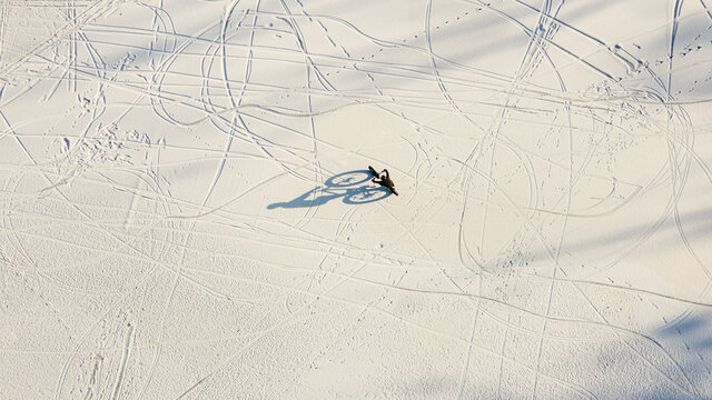 Aerial view a man riding a bicycle on snowy lake