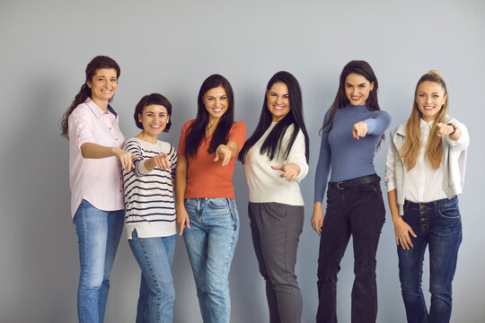 We need you. Join us. Group portrait of positive smiling confident young women standing in studio and pointing fingers at camera, choosing and inviting you to become member of happy successful team