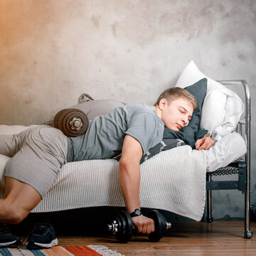 The athlete is lounging, resting  with dumbbells and postponing training at home. The concept of proastination, sports laziness