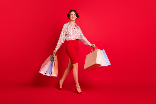 Full length body size view of lovely elegant cheerful brown-haired girl carrying buyings bargain isolated over bright red color background