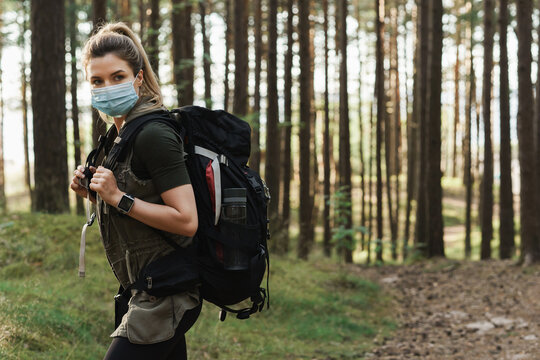 Woman hiker with a backpack wearing prevention mask during her hike in forest