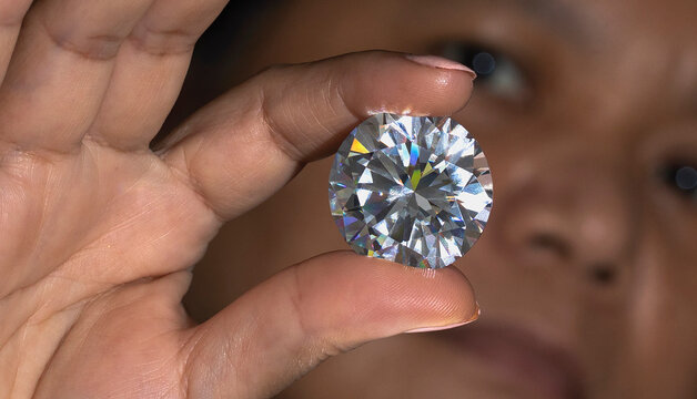 Close up face of Asian woman watching at round cut large size diamond. Big size polished brilliant in hand closeup view. Luxury gem stone. High quality photo