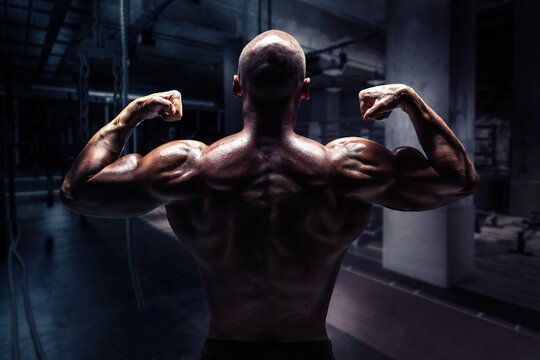 Rear View Of Shirtless Body Builder Flexing Muscles In Gym