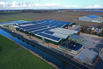 Obraz Flower bulb company with solar panels in a row on a roof. Photo taken with a drone - fototapety do salonu