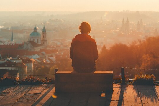 man looks at the city at sunset