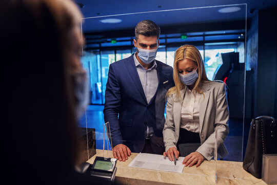 A middle-aged couple in formal wear with face masks checking in the hotel.