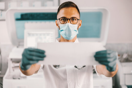 Dedicated male lab assistant with rubber gloves and face mask standing in laboratory and holding paper with results. Corona virus outbreak concept.