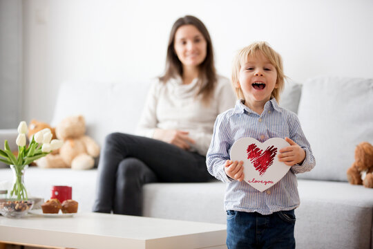 Beautiful blond boy, giving mother flowers and box with little gift for mothers day