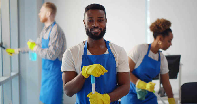 Portrait of african cleaner in apron and gloves holding mop and smiling at camera working in office