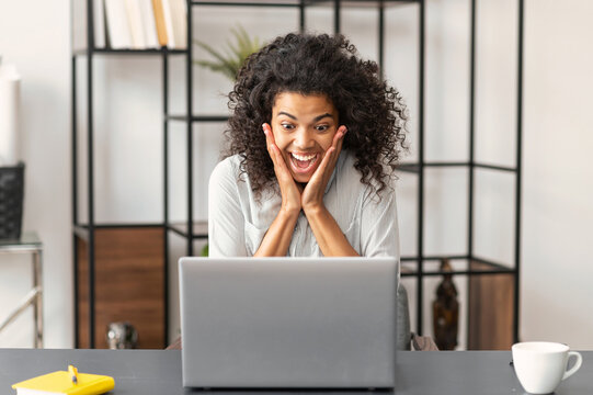 Surprised young African American businesswoman with eyes and mouth wide open touching face with hands, sitting at the desk, checking the news online, looking at the laptop screen and cannot believe