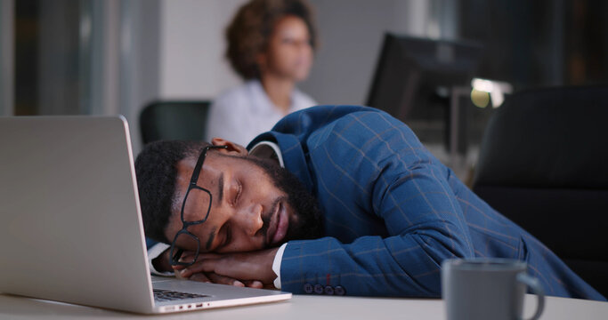Young african businessman with eyeglasses worked late and fell asleep on desktop