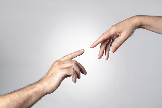 a man's and a woman's hand touching each other with their fingertips