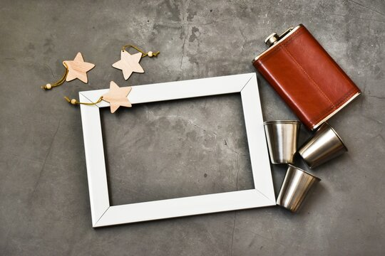 White frame with a flask and glasses, stars on a concrete background. Close up, top view. Copy space. Holidays concept Happy Father's Day, 23 February.