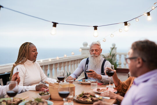 Multiracial senior people enjoy barbecue together at home on patio