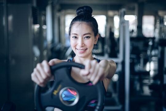 Portrait Of Woman Exercising With Weights In Gym