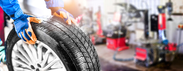 Fototapeta Auto mechanic working in garage and changing wheel alloy tire. obraz