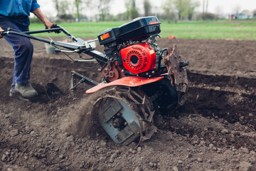 Farmer driving small tractor for soil cultivation and potato planting. Spring preparation. Outdoor work