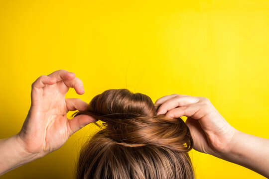 A woman makes a messy hair bun on her head. Yellow background. Copy space. Trend color of the year 2021