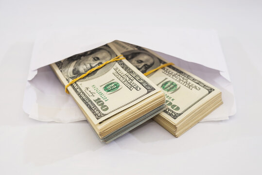 two bundles of dollars tied with an elastic band in a white envelope on a white background