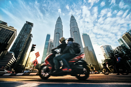 People Riding Motor Cycle On Road Against Buildings In City