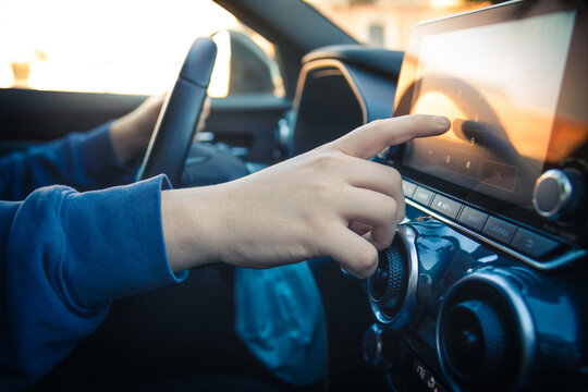 Teen drive a car and use infotainment. Young man reading messages and make phone call while driving. Dangerous behavior, accident risk. Danger, transgression, youth, distraction concept. Focus on hand