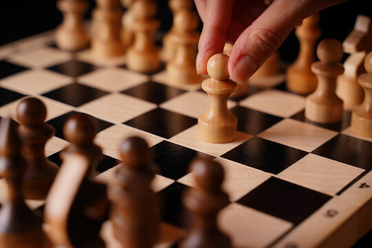 Close up of white and black chess pieces on board. Selective focus on first move of white pawn on chessboard. Concept of intelligent, logical and strategic game.