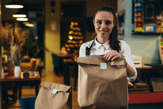 woman holding food in paper bag prepared for delivering