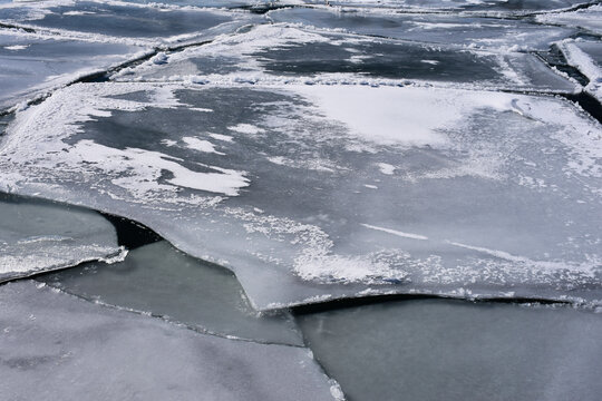 Sheets of thin ice seen on a river. Abstract concept of boating safety, drowning, danger.