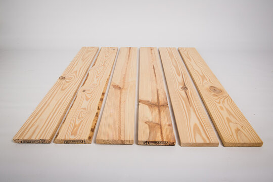 Unfinished raw pine lumber on a solid white background
