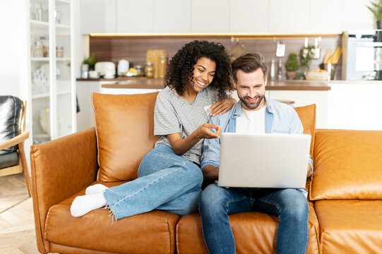 Cheerful diverse couple in love spends leisure time online with a laptop at home. Young woman and man look at the laptop screen and laugh sitting on the sofa, watching comedy movies, funny videos
