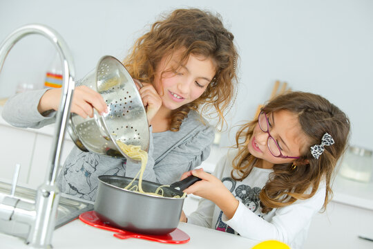 Two girls tipping spaghetti from collander into saucepan