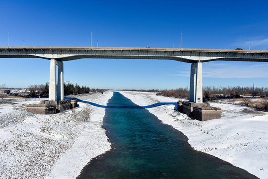 The Welland Canal is drained for the winter, allowing maintenance to be completed. St. Catharines Garden City Skyway runs above.