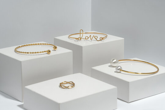 Golden bracelets and ring on white cubes eith copy space