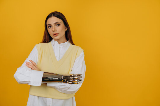 Portrait of a beautiful young woman with a silver bionic prosthetic arm in a white shirt on a yellow background. A confident woman looks at the camera with her hands folded. Copyspace.